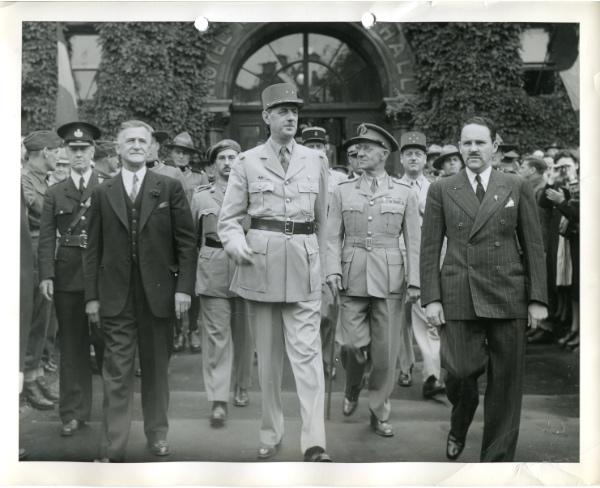 12 juillet 1944, vers 10h15, De Gaulle quitte l'hôtel de ville de Québec. De gauche à droite: Le maire Lucien Borne, le général de Gaulle, le major-général T.-L. Tremblay (au 2e rang) et le Dr André Simard, l'époux de Marthe Caillaud-Simard, fondatrice du premier Comité de la France libre, qui était alors à Alger.