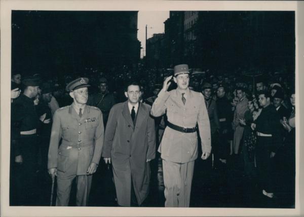 12 juillet 1944 - Sur la rue menant de l'archevêché à l'hôtel de Ville de Québec, Gaulle salue la foule massée et les militaires qui lui font une haie d'honneur. Il est accompagné par le major-général Tremblay et par le ministre québécois des Terres et Forêts, Wilfrid Hamel, futur maire de Québec.